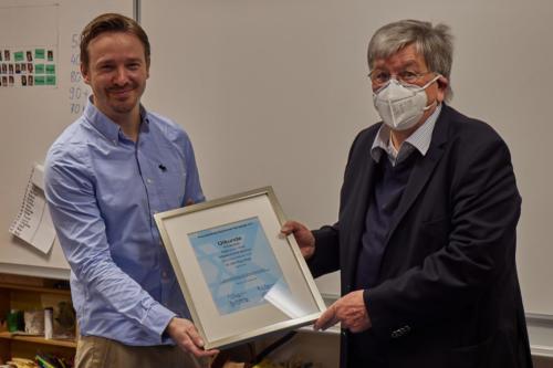 Tammo Grabowski und Volker Brüggemann mit der Urkunde für die Schule